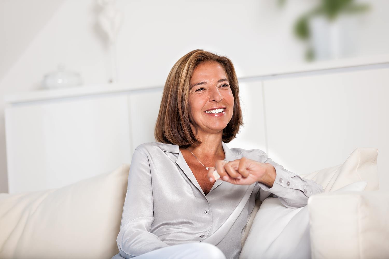 eine junge business trainerin wird auf einem hellen sofa portraitiert