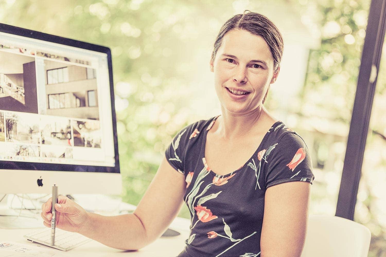 eine junge architektin in einem architekturbüro in der innenstadt von leipzig. das portraitfoto am arbeitsplatz wurde bewusst wvor einem schönen grossen fenster aufgenommen.